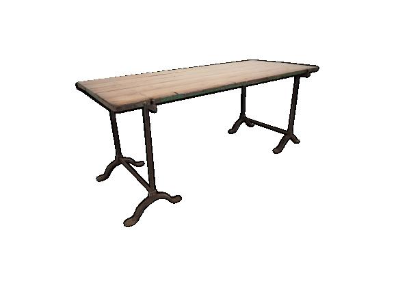 Table industrielle avec des pieds en fonte et un plateau en bois réversible